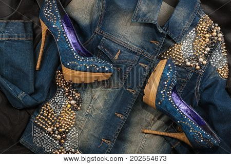 Shoes and jacket from denim fabric inlaid rhinestones lying on a black silk. Glamorous women's fashion