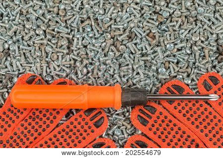 Screwdriver and work gloves lie on a pile of screws. Background screen saver