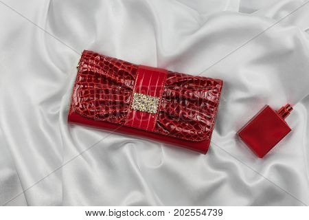 Bag of lacquered leather and red perfume lying on white silk. Handbag for women and bottle of scent top view. Accessories in modern style. Fashion and glamour concept