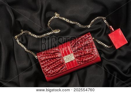 Bag of lacquered leather and red perfume lying on black silk. Handbag for women and bottle of scent top view. Accessories in modern style. Fashion and glamour concept