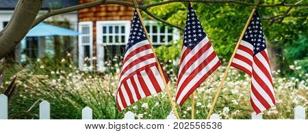 Flags in a southern California neighborhood sitting on a fence.
