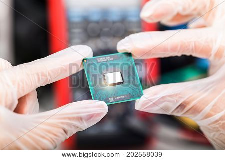 Creative abstract digital computer PC technology and electronic industry manufacturing and production business concept: macro view of the CPU processor in hand in gloves with selective focus effect