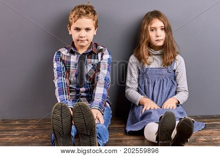 Cute sister and brother sitting near wall. Adorable little kids sitting on wooden floor. Little boy and girl sitting together and looking at camera.