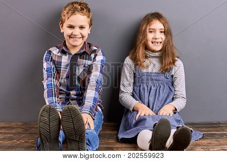 Portrait of smiling little brother and sister. Studio shot of happy little brother and sister sitting on floor. Beautiful kids, sister and brother.