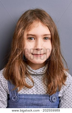 Studio shot of pretty little girl. Charming brown hair little girl on grey background looking at camera. Concept of childishness and kids innocence.