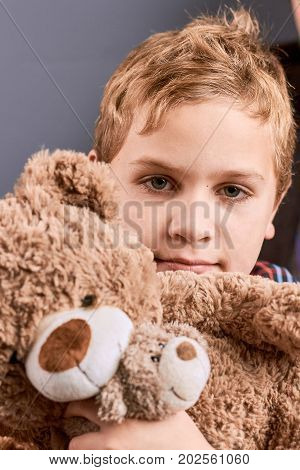 Little handsome boy hugging teddy. Portrait of adorable little boy hugging plush teddy bear. Cute little boy with toy.
