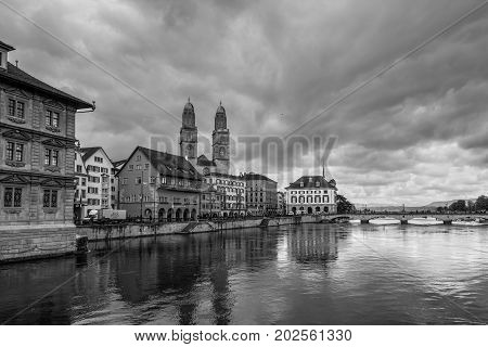 Zurich Switzerland - May 24 2016: Architecture of Zurich in overcast rainy weather the largest city in Switzerland and the capital of the canton of Zurich Switzerland. Limmat river in the foreground. Black and white photography dramatic sky.