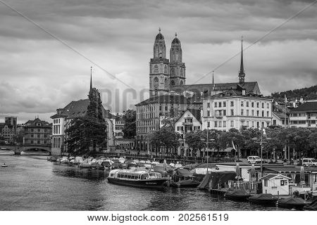 Zurich Switzerland - May 24 2016: View of historic Zurich city center with Grossmunster Church and Limmat river on a cloudy rainy day Zurich Switzerland. Black and white photography.