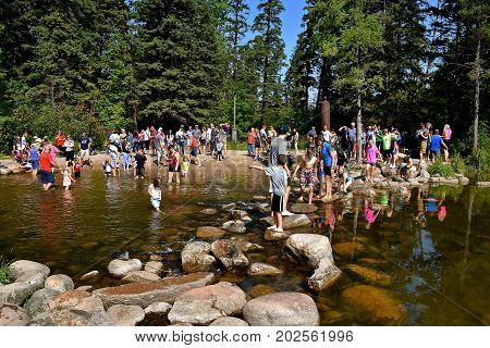 ITASCA, MINNESOTA: SEPTEMBER 1, 2017: Tourists visit and cross the rocks at the  headwaters of the Mississippi River in Itasca State Park, Minnesota's first, set  by the Minnesota Legislature on April 20, 1891.