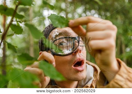 Picture of young botanist with magnifying glass in forest on summer day