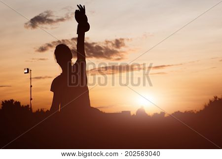 the girl is engaged in aerobics on a sunset background. silhouette