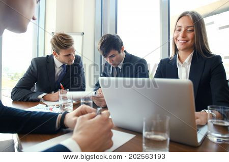 Businesspeople discussing together in conference room during meeting at office poster