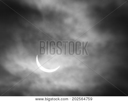 partial solar eclipse with sun through clouds