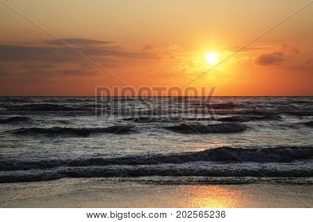 Sunset with clouds on the North sea. Landscape with sun, beach and high waves