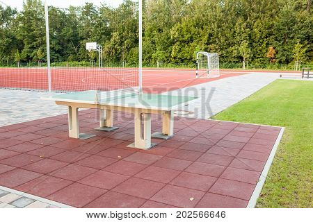In a park there is a table tennis for ping pong to play