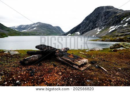 Charred peaces of timber used for a camp fire in the mountains of norway with a lake in the background