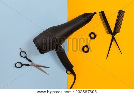 Styling hair with scissors, dryer and tools in barbershop on blue and yellow paper background. Top view. Copy space. Flat lay. Still life. mock-up