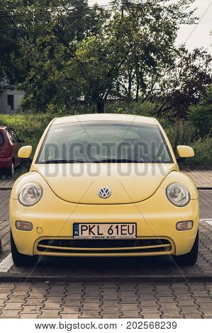 Yellow new Volkswagen Beetle car parked on a parking spot on August 2017 in Poznan Poland in classic film look