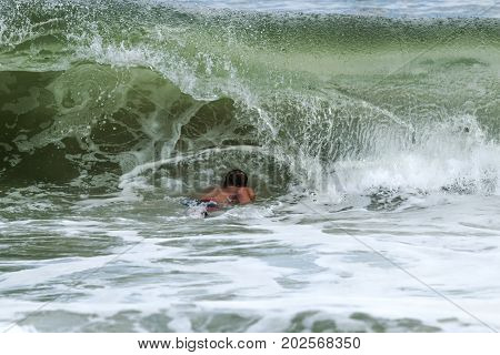 A surfer has to go under a wave as it curls over him to be able to get out further into the atlantic ocean off of Fire Island New York.