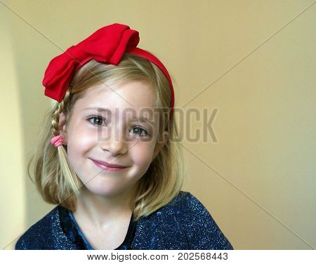 Portrait of a little six years old smiling cute blond girl with a red bow on his head on beige painted wall background.
