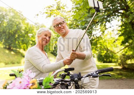 active old age, technology and lifestyle concept - happy senior couple walking with fixie bicycles taking selfie by smartphone at summer park