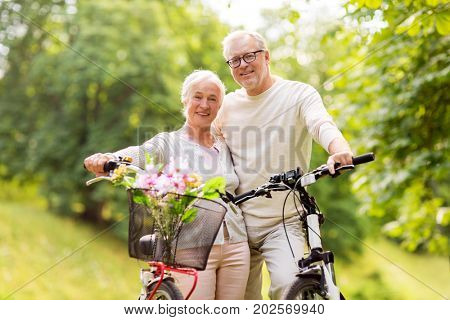 old age, people and lifestyle concept - happy senior couple with bicycles at summer city park