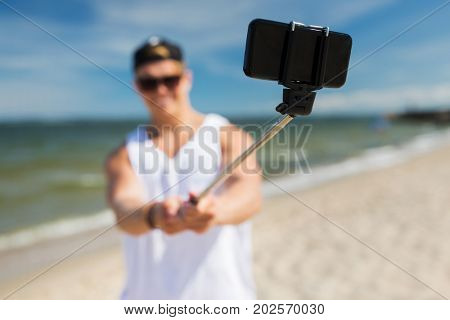 technology, summer holidays and people concept - happy young man taking picture by smartphone on selfie stick on beach