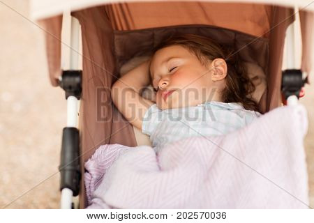 childhood, rest and people concept - little child or baby sleeping in stroller outdoors