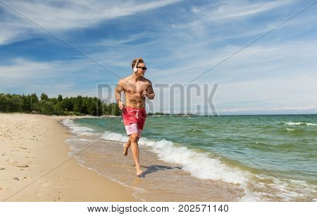fitness, sport, people and healthy lifestyle concept - happy young man with headphones running along summer beach