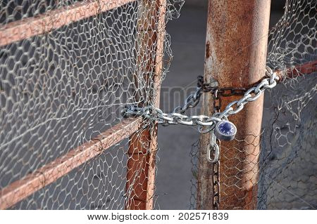 Rusty gate closed with a chain and combination lock