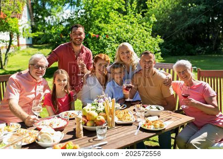 leisure, holidays and people concept - happy family having festive dinner or summer garden party and celebrating