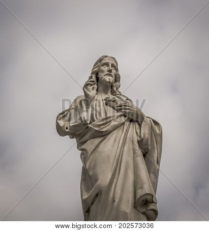 Jesus statue with raised fingers on a cloudy day