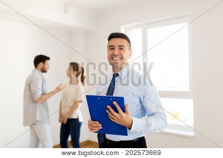 real estate, mortgage and people concept - happy smiling realtor with clipboard and couple at new home