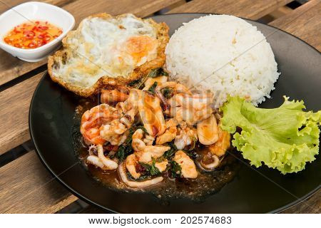 Rice topped with stir-fried combination of pork, chicken, squid, shrimp, basil and fried egg. Thai food. (Focus on fried basil and shallow depth of field)