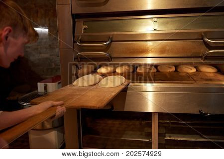 food, cooking and baking concept - baker with peel putting yeast dough into bread oven at bakery kitchen