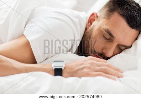 people, bedtime and rest concept - close up of man with smartwatch sleeping in bed