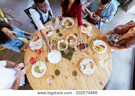 leisure, food and people concept - group of happy international friends eating at restaurant table