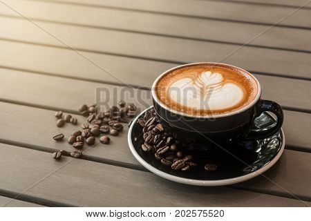 Hot latte coffee (or cappuccino) in a black cup with latte art and roasted coffee beans on gray wooden table background.