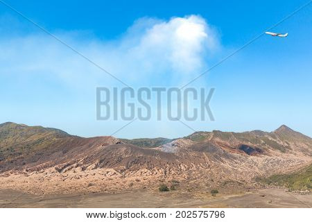 Landscapes of Mount Bromo volcano (Mt.) in a day time blue clouds sky with erupting smoke and airplane located in Bromo Tengger Semeru National Park East Java Indonesia.
