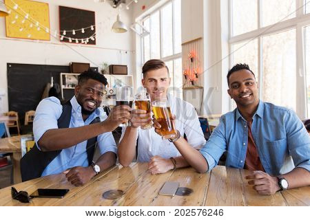 people, friendship and celebration concept - happy male friends drinking beer and clinking glasses at bar or pub