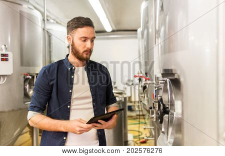 manufacture, business and people concept - man with tablet pc computer working at craft brewery or beer plant