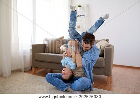family, childhood, fatherhood, leisure and people concept - happy father and little son playing and having fun on sofa at home