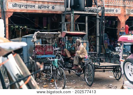 JAIPUR RAJASTHAN INDIA - MARCH 10 2016: Horizontal picture of two indian men working as rickshaw in Jaipur known as pink city of Rajasthan in India.