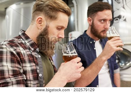 production, manufacture, business and people concept - men testing and drinking non-alcoholic or craft beer at brewery