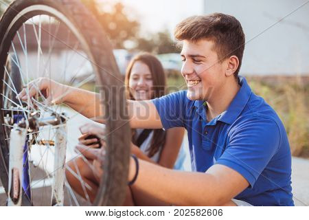 Teenager boy repair tire on bicycle female friend sitting next to him summer outdoor photo
