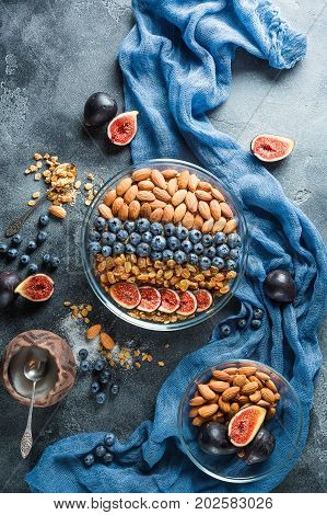 Natural tasty breakfast with muesli, berries and nuts on dark background. Flat lay, Top view