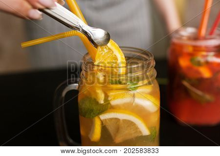 Waiter puts piece of sliced orange into jar of fruit cocktails. Fresh citrus and strawberry cold drink with mint and ice on table, refreshment and satisfying thirst in summer
