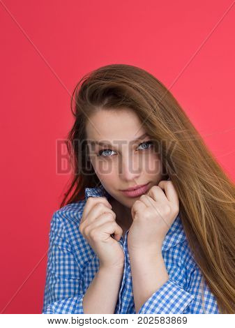 Portrait of a beautiful positive young woman while playing with her long silky hair isolated on red background