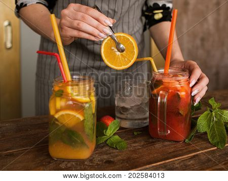 Waiter preparing fruit cocktails in restaurant. Fresh citrus and strawberry cold drink with mint and ice on wooden table, concept of refreshment and satisfying thirst in summer