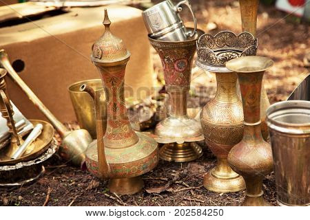 Antique Indian handicraft etched vases and surahi jug at a flea market. Old brass tableware collectibles at a garage sale